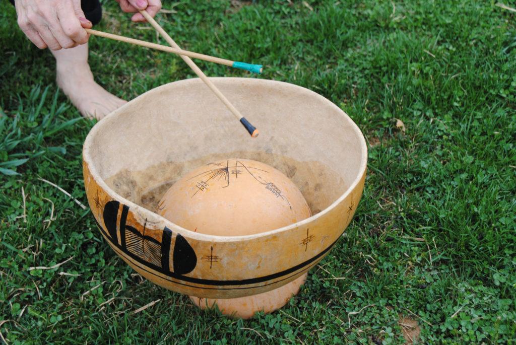 Playing water gourd drum